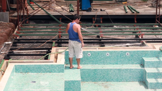 vídeos y material grabado en eventos de stock de ms shot of construction worker hosing down swimming pool area in construction zone / montezuma, punteranes, costa rica - kelly mason videos