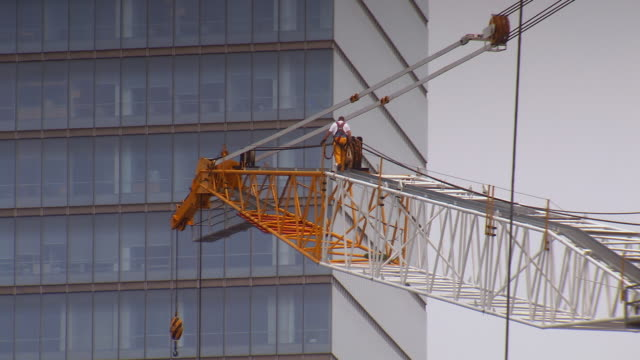 vidéos et rushes de ms shot of construction worker walking on crane above construction site of one world trade center with office building / new york, united states - gratte ciel