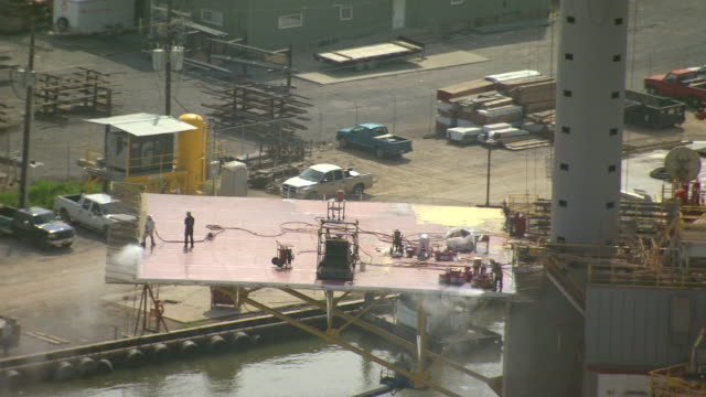 MS AERIAL Shot of construction workers repairing oil platform at port fourchon / Louisiana, United States