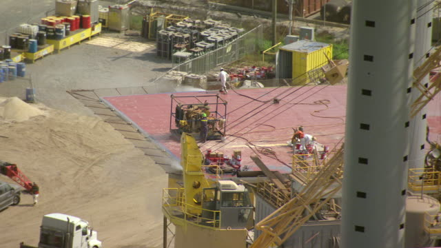 MS AERIAL ZO Shot of construction workers repairing oil platform at port fourchon / Louisiana, United States