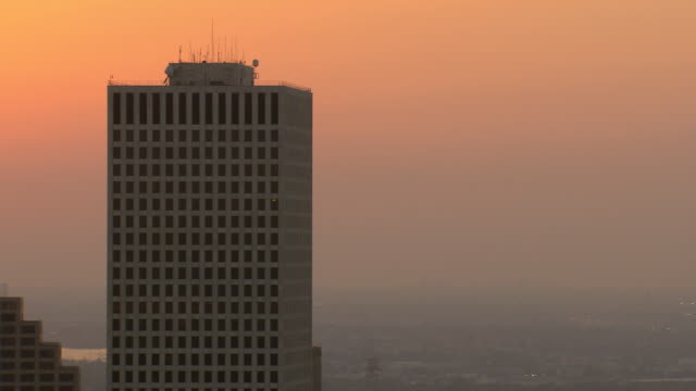 MS AERIAL ZO Shot of contemporary office building and downtown skyline with sun setting / New Orleans, Louisiana, United States