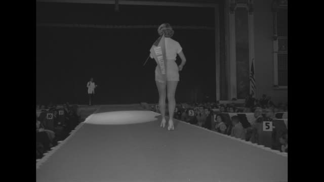 shot of contestants' legs in row on stage / vs contestants walking up and down runway in shorts and sweater tops holding college pennants / shot of... - contestant stock videos and b-roll footage
