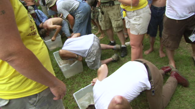 ws zi shot of contestants trying to be fastest to taking out pigs feet resting at bottom of box filling with water using their mouth only during summer redneck games / dublin, georgia, united states - hillbilly bildbanksvideor och videomaterial från bakom kulisserna
