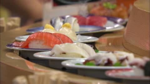 shot of conveyor belt sushi in tokyo, japan - japanese food stock videos & royalty-free footage