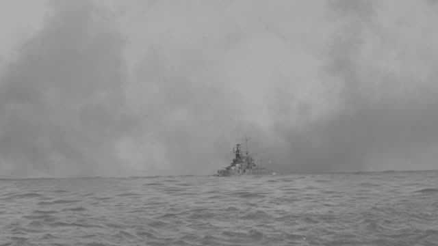 MS TS PAN Shot of convoy of military ship as they maneuver through smoke as shell falling from sky