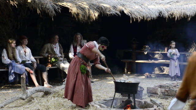 ms shot of cooking in camp life at medieval party showing marriage of 1475 with medieval clothing / landshut, bavaria, germany - 中世点の映像素材/bロール