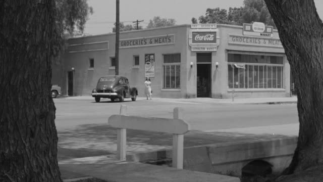 MS Shot of corner store with street principal actor enters
