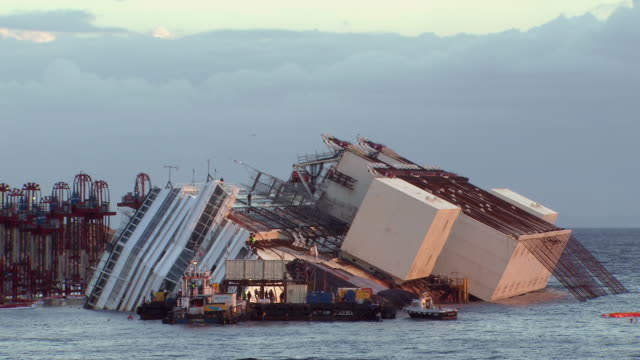 MS Shot of Costa Concordia cruise ship lying on its starboard side in early morning / Giglio Porto, Tuscany, Italy