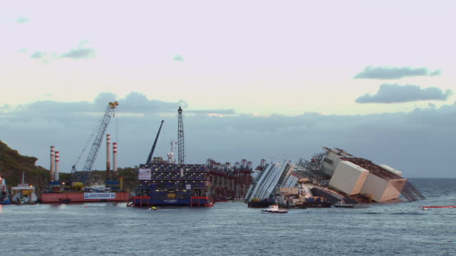 ws shot of costa concordia cruise ship surrounded by parbuckling equipment in early morning / giglio porto, tuscany, italy - capsizing stock videos and b-roll footage