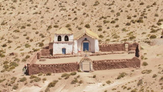 ws shot of country church at machucca in high andes and tourist looking at it / san pedro de atacama, norte grande, chile - san pedro de atacama stock videos & royalty-free footage