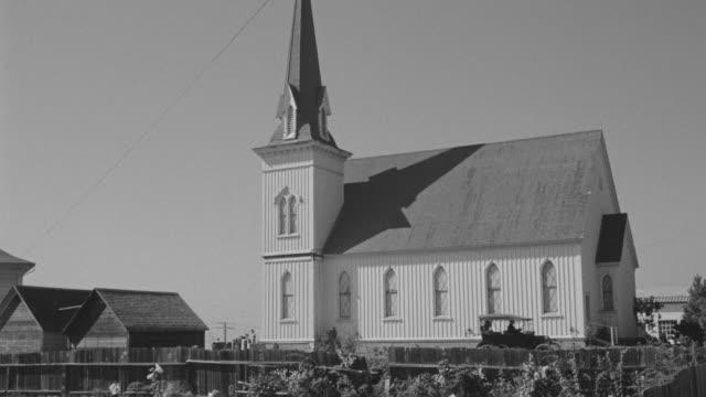 ms shot of country church with people coming out of church - tornspira bildbanksvideor och videomaterial från bakom kulisserna