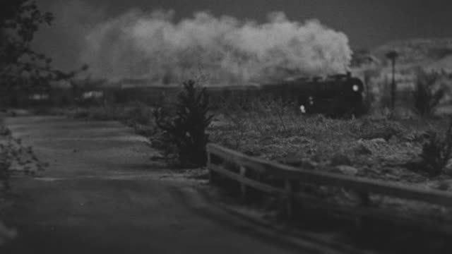 MS Shot of Country road as train coming from back side on railroad tracks along side (miniature)