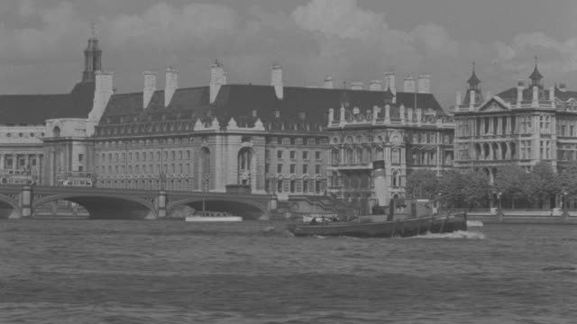 ws shot of county hall building in london from across thames river and boats floating at thames river - tugboat stock videos and b-roll footage