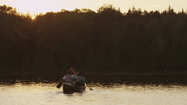 ms shot of couple canoeing at sunset on long pond / maine, united states - maine stock videos & royalty-free footage