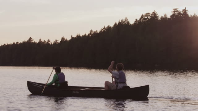 ms pan shot of couple canoeing at sunset on long pond / maine, united states - maine stock videos & royalty-free footage