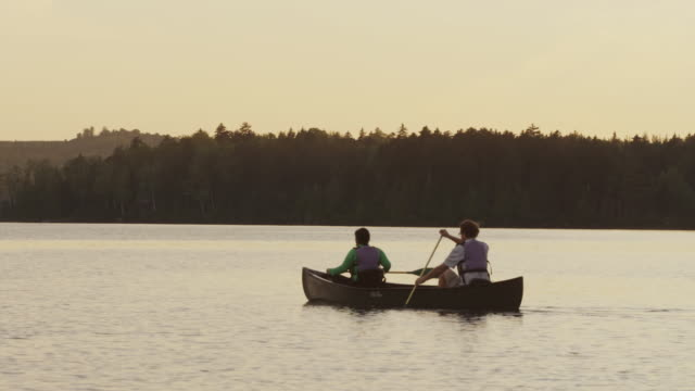 ms ts shot of couple canoeing at sunset on long pond / maine, united states - maine stock videos & royalty-free footage