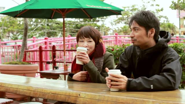 MS Shot of Couple drinking coffee and talking / Chatan, Okinawa, Japan