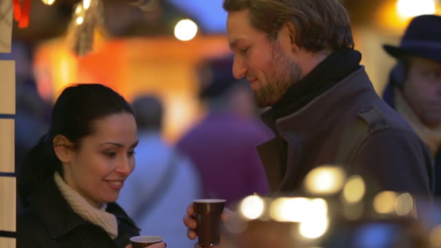 CU Shot of Couple drinking, laughing and talking at Christmas market / Potsdam, Brandenburg, Germany