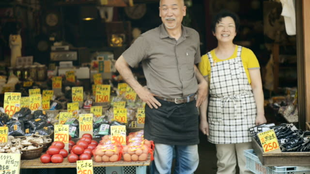 ms shot of couple engaged in greengrocer is standing in storefront / toyooka, hyogo, japan - giappone video stock e b–roll