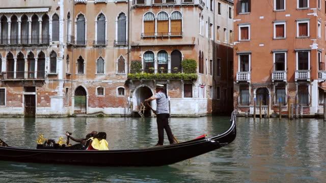 ms shot of couple enjoying gondolas journey on canal grande near rialto / venice, veneto, italy - ヴェネツィア点の映像素材/bロール