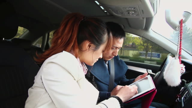 MS Shot of couple in car reading map on tablet computer and pointing / Xian, China