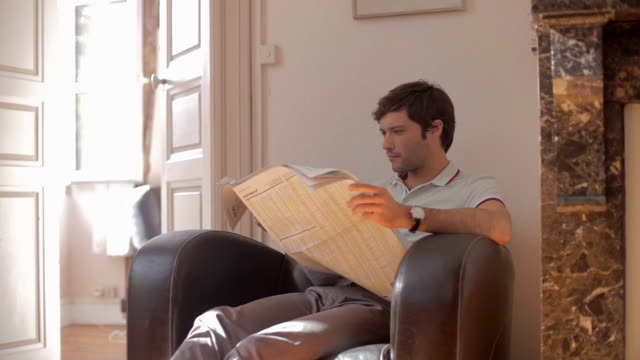 vidéos et rushes de ms pan shot of couple in lounge surfing internet and reading / toulouse, haute garonne, france - journal