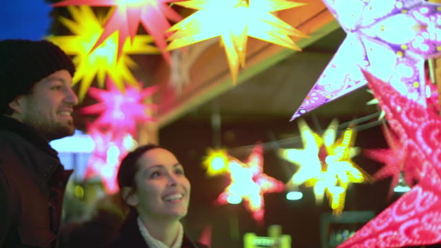 cu ts shot of couple looking at star lights at christmas market booth / potsdam, brandenburg, germany  - star shape stock videos & royalty-free footage