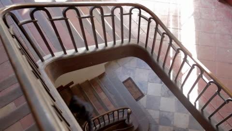 ms ua pan shot of couple meet and hug on stairway landing / toulouse, haute garonne, france - 踏む点の映像素材/bロール