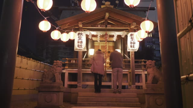 ms zo shot of couple praying in temple, tokyo , japan - shrine stock videos & royalty-free footage
