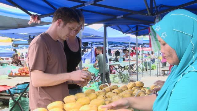 ms shot of couple sampling fruit in market / kota kinabalu, sabah, malaysia  - kota kinabalu stock videos and b-roll footage