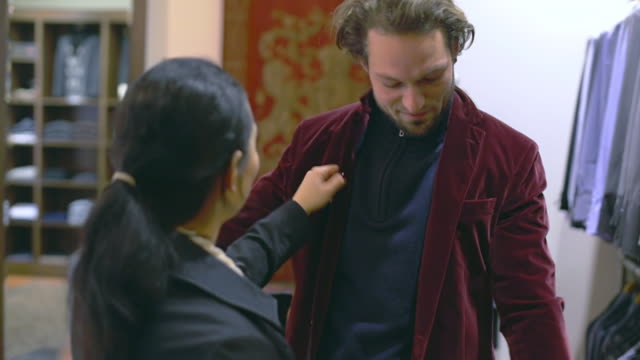 vidéos et rushes de cu shot of couple shopping inside store for men's suits, man trying on dark red suit / potsdam, brandenburg, germany  - veste et blouson