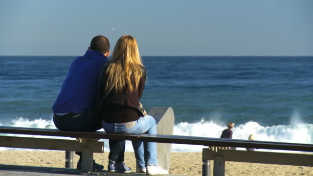 MS Shot of couple sitting on bench and watching sea at Barceloneta / Barcelona, Catalonia, Spain
