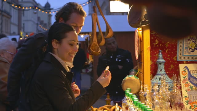 MS Shot of Couple smelling fragrances at booth at Christmas market / Potsdam, Brandenburg, Germany