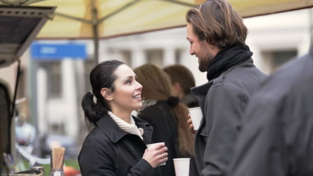 CU PAN Shot of Couple talking and laughing over coffee at outdoor market / Potsdam, Brandenburg, Germany