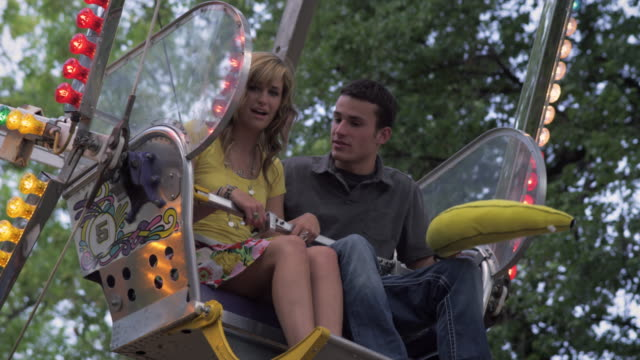 shot of couple talking on a stopped ferris wheel. - teenage couple stock videos & royalty-free footage