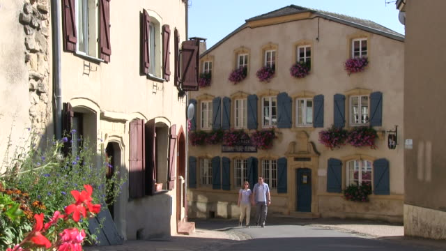ms shot of couple walking at old town / rodemack, lorraine, france - lorraine stock-videos und b-roll-filmmaterial