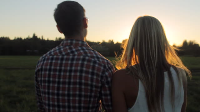 ms pov slo mo ts shot of couple walking in countryside at sunset / langley, british columbia, canada - falling in love stock videos and b-roll footage
