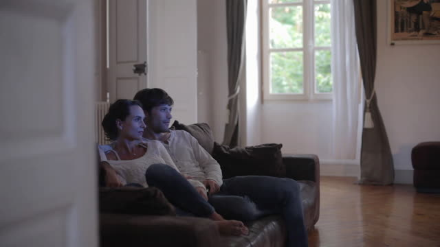 ms pan shot of couple watching tv / toulouse, haute garonne, france - guardare la tv video stock e b–roll