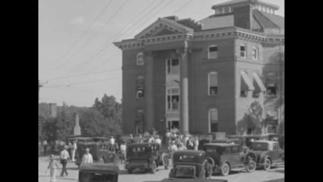 Shot of courthouse and crowd in front of it / four shots of Libby Holman Reynolds walking through crowd towards courthouse wearing black veil and...