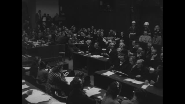 shot of courtroom judges at long table on left german lawyers for nazi defendants sitting at tables on left of judges pan cross to defendants sitting... - processi di norimberga video stock e b–roll
