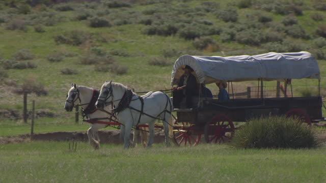 vídeos y material grabado en eventos de stock de cu aerial ts ds shot of covering wagon pulled by horses at chimney rock / nebraska, united states - expansión hacia el oeste