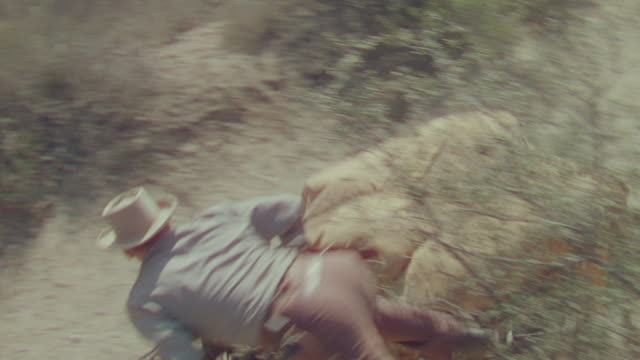 ms shot of cowboy jumping on running buggy - espansione verso l'ovest video stock e b–roll