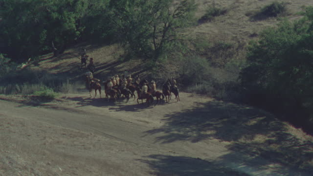 ms ha shot of cowboys discussing and moving towards desert - espansione verso l'ovest video stock e b–roll