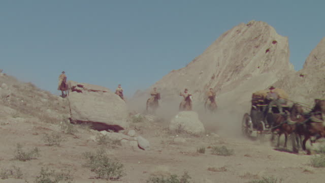 ws shot of cowboys on horseback chasing horse and buggy speeding through desert  - espansione verso l'ovest video stock e b–roll
