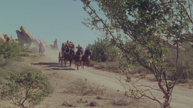 ws pan shot of cowboys on horseback chasing horse and buggy speeding through desert  - kutsche stock-videos und b-roll-filmmaterial