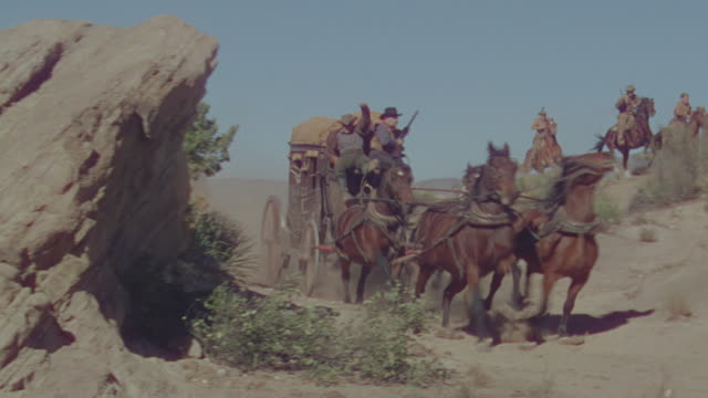 ms shot of cowboys on horseback chasing horse and buggy speeding through desert  - espansione verso l'ovest video stock e b–roll