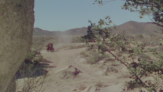 vidéos et rushes de ws shot of cowboys on horseback chasing horse and buggy speeding through desert  - voiture attelée