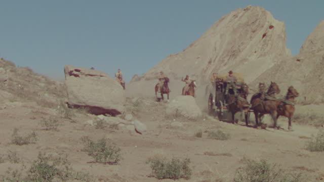 vidéos et rushes de ws shot of cowboys on horseback chasing horse and buggy speeding through desert  - voiture hippomobile