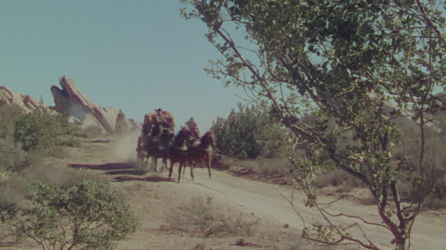 WS PAN Shot of cowboys on horseback chasing horse and buggy speeding through desert