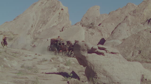 vidéos et rushes de ws pan shot of cowboys on horseback chasing horse and buggy speeding through desert  - voiture attelée